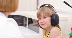 young girl with over-ear headphones on.