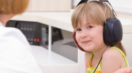 young girl with over-ear headphones on. thumbnail crop.