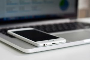 white smart phone resting on an open laptop.